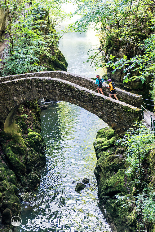 Trail running tour in the Jura Mountains of Switzerland. The Jura are an old, small mountain group in northwest Switzerland. Passing through the Gorges de L'Areuse on a small stone bridge.