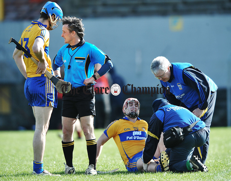 Clare's Fergal Lynch is treated for an injury as Darach Honan looks on during their National League game against Down at Cusack park. Photograph  by John Kelly.
