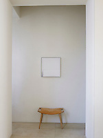 A small wooden stool with a leather seat is placed beneath an abstract painting in the hall