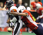 SIOUX FALLS, SD - JUNE 16:  Jermiah Price #56 from the Sioux Falls Storm forces a fumble on quarterback James McNear #3 of the Omaha Beef in the second quarter Saturday night at the Sioux Falls Arena. Sean Kelly (not pictured) picked up and returned the fumble for a touchdown. (Photo by Dave Eggen/Inertia)