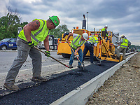Asphalt contractors lay asphalt along a section of 3C Highway through Blendon Township, Ohio, as part of an upgrade to an interstate highway outerbelt loop intersection. <br /> <br /> Photo Copyright 2015 Gary Gardiner. Not to be used without written permission detailing exact usage. Photos from Gary Gardiner, may not be redistributed, resold, or displayed by any publication or person without written permission. Photo is copyright Gary Gardiner who owns all usage rights to the image.