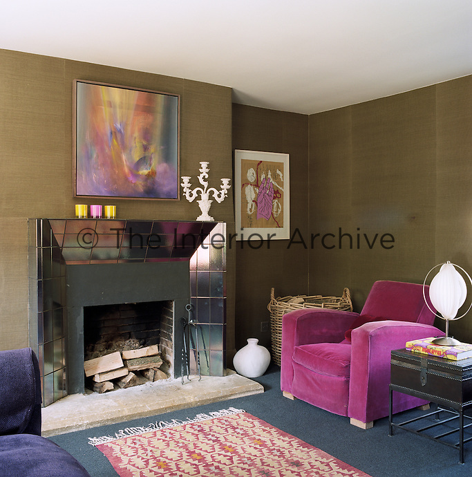 A contemporary fireplace with a surround of lustre tiles is the focal point of the living room
