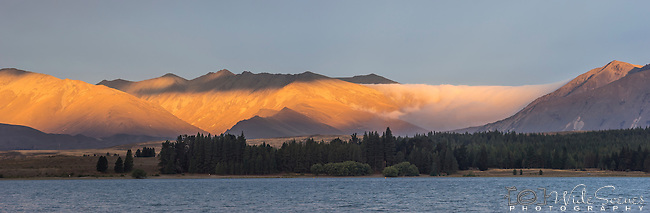 Golden light approaching sunset on the low clouds at Lake Tekapo, Canterbury Region, South Island, New Zealand