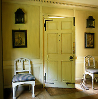 A pair of painted gothic chairs flank the open front door in the entrance hall