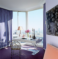 In the master bedroom a large floor-to-ceiling bay window affords panoramic views over Manhattan