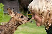 Rehkitz, Reh-Kitz, verwaistes, pflegebedürftiges Jungtier wird in menschlicher Obhut großgezogen, Kind, Junge mit Kitz im Garten, Tierkind, Tierbaby, Tierbabies, Europäisches Reh, Ricke, Weibchen, Capreolus capreolus, Roe Deer, Chevreuil