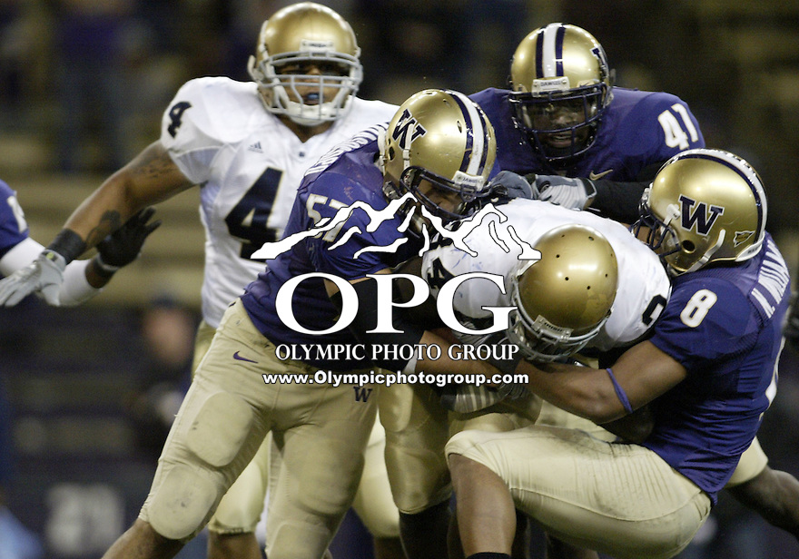 October 25, 2008:   Washington's #57 Trenton Tuiasosopo, #41 Victor Aiyewa and #8 Nate Williams worked together to bring down Notre Dame running back #34 James Aldrige.  Notre Dame defeated Washington 33-7 at Husky Stadium in Seattle, Washington..