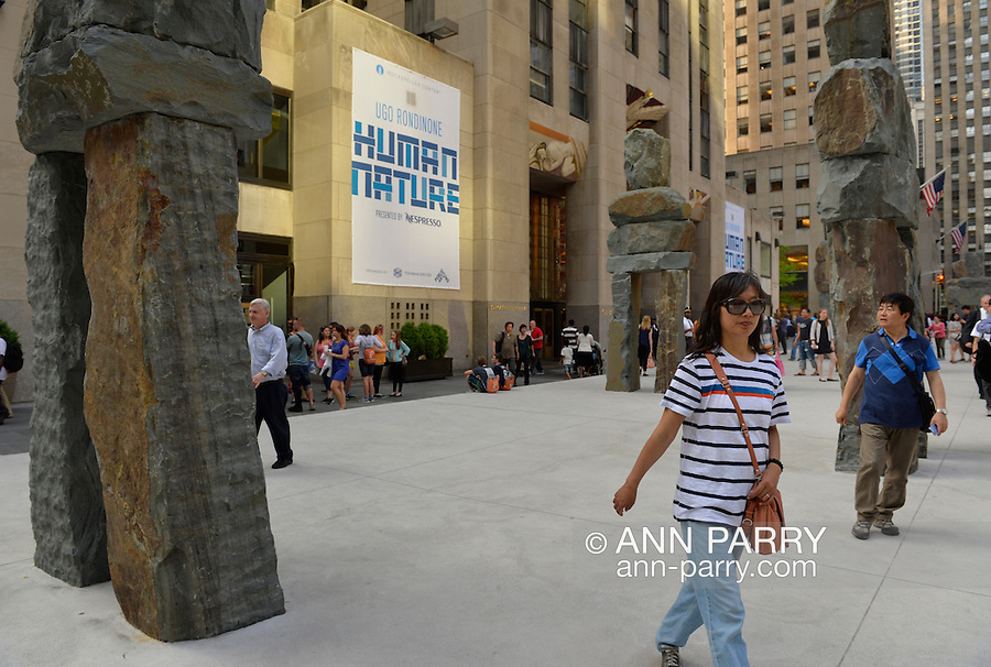 NYC, New York, U.S.  21st May 2013. Visitors are walking through Human Nature, an outdoor art installation, by artist Ugo Rondinone, specifically created for its location in front of 30 Rockefeller Plaza, and features nine colossal structures. The 16-foot to 20-foot tall human shaped stone figures are made of roughly shaped slabs of bluestone and each weigh up to 30,000 pounds. This free exhibit, presented by Nesporesso and organized by Public Art Fund and Tishman Speyer, is on view through July 7, 2013.