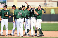 Clinton LumberKings second baseman Martin Peguero (7) is mobbed by teammates including Justin Seager (17) and Brett Thomas (8) after a game winning hit during a game against the Beloit Snappers on August 17, 2014 at Ashford University Field in Clinton, Iowa.  Clinton defeated Beloit 4-3.  (Mike Janes/Four Seam Images)