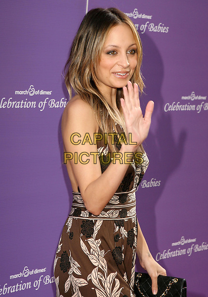 NICOLE RICHIE.attending the March of Dimes Celebration of Babies held at the Four Seasons Hotel,  Los Angeles, California, USA, 7th November 2009..half length hand waving brown pattern print dress chanel black clutch bag .CAP/ADM/MJ.©Michael Jade/Admedia/Capital Pictures
