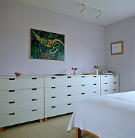 In the bedroom a row of drawers from Habitat stands beneath a painting by Melvin Nutbeam