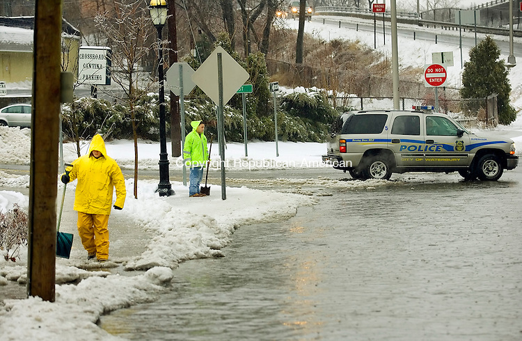 WATERBURY, CT. 13  February 2007-021308SV02--City workers try to clear drains as a police officer blocks a pond that was forming at the end of Field Street in Waterbury Wednesday.<br /> Steven Valenti Republican-American