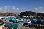 Old sea defence castle over looking rowing and fishing boats in the harbour at El Cotillo, Fuerteventura, Canary Islands, Spain.