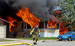 A Villiage of Allouez firefighter runs for a hose line at a multi-trailer fire on Miron Street in Bellevue on June 17, 2006.