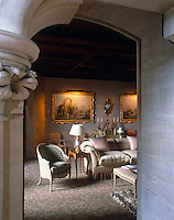 A glimpse through a stone door frame into a small comfortably furnished drawing room