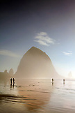USA, Oregon, Pacific City, individuals walk along Pacific City Beach with Haystack Rock in the distance