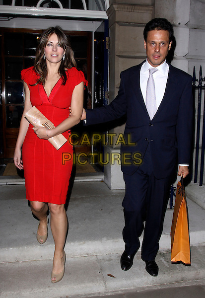 ELIZABETH HURLEY & ARUN NAYER.Leaving The Italian Touch Tod's Boutique after party dinner, Spencer House, St. James Place, London, England, UK, .November 4th 3009..full length red dress beige peep toe shoes clutch bag suit blue tie navy married couple husband wife Liz shopping carrier bag.CAP/AH.©Adam Houghton/Capital Pictures.
