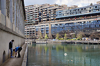 "Switzerland. Geneva. A police officer search the belongings of a convict man who got arrested while selling drugs in the streets. The prisoner is handcuffed and stands close to the "" Batiments des Forces Motrice s"". Modern architecture and the Rhone river. Swan and ducks swimm in the water. The inmate is an arab man from the Maghreb area. A frisk search (also called a patdown or pat down) is a search of a person's outer clothing wherein a person runs his or her hands along the outer garments to detect any concealed weapons or contraband. 3.05.12 © 2012 Didier Ruef.."