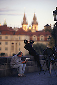 Prague, Czech Republic; woman in black taking a picture of the Charles Bridge, man sitting on a stool reading.