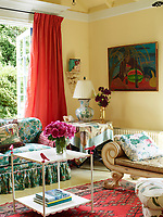 The yellow sitting room, with its exposed ceiling rafters is light and airy. Magenta taffeta curtains and bold chintz upholstery bring accents of pink colour to the room.
