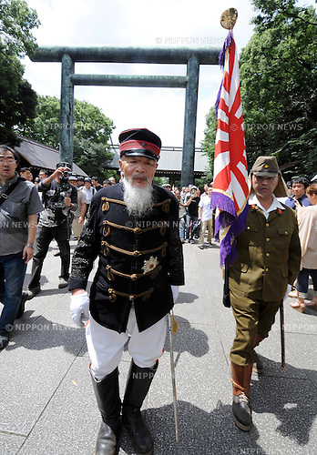 August 15, 2012, Tokyo, Japan - Dressed in old military uniform, two Japanese with an ensign make their way to Tokyo's Yasukuni Shinto Shrine, which honors the war dead, as the nation observes the 67th anniversary of the end of World War II on Wednesday, August 15, 2012.  (Photo by Kaku Kurita/AFLO) FYJ -mis-