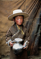 Tibet, Kham, 2005 Tibetan nomad boy in Degang Valley, near Litang. This sweet little nomad boy hovers close to his mother in their traditional yak hair tent as he helps her make the tea.