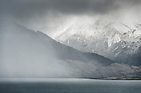 Moody weather at Lake Wanaka with snow covered mountains, Central Otago, New Zealand