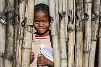 MADAGASCAR, village AMBOHITSARA at canal des Pangalanes, tribe  ANTAMBAHOAKA , girl with school books looking through bamboo fence / MADAGASKAR, Mananjary, Stamm der ANTAMBAHOAKA im Dorf AMBOHITSARA am canal des Pangalanes, Maedchen mit Schulheften schaut durch einen Bambus Zaun