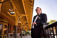 An opera singer stands at a train station in his home town.