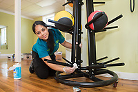 Sonja Then,'21, cleans the exercise balls in the gym of the Martin Luther King Center as she participates in the Salve Regina University Exploration Day in Newport.