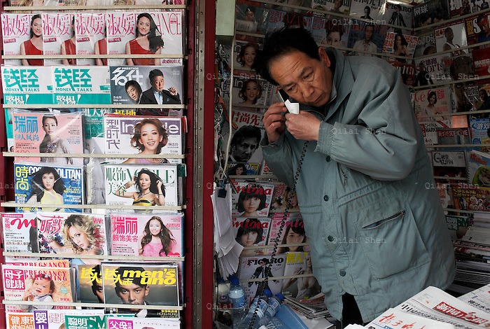 A news paper seller takes a phone call in his booth, a majority of which displays women's magazines, in Shanghai, China on 04 April, 2009. More than any other region in the country, Shanghai's media outlets are vigorously censored  by the local government and the communist party, leaving editorial freedom only to those publications gear towards fashion and lifestyle.
