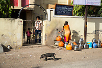 A young girl collects water from a small tap outside a hospital in the city of Latur. Many residents of the city are without water however those that have access often supply their excess to others for free.