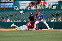Frisco RoughRiders first baseman Ronald Guzman (11) waits for a pickoff attempt throw as Johan Mieses (41) dives back to the bag with umpire Isaias Barba looking on during a Texas League game against the Springfield Cardinals on May 5, 2019 at Dr Pepper Ballpark in Frisco, Texas.  (Mike Augustin/Four Seam Images)