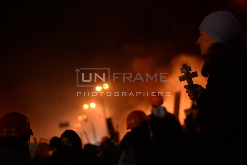 A protester holds a cross. Many Orthodox faithful participated in the most intense moments of the battle with traditional orthodox choirs in the middle of the  battlefield of Maidan square.  Kiev, Ukraine