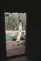 Jasai walks across a narrow bridge over cenote water toward one of her father´s houses. Photos for Jasai´s catalogue of the houses of Memo and the surrounding area