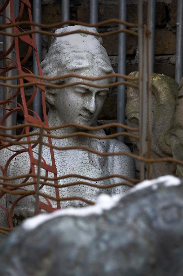 Frankrijk, Parijs, 30 jan 2010.Vlooienmarkt van Parijs. Mooi beeld van vrouw achter metalen hekwerken..Le marché aux puces de Saint-Ouen.Foto (c)  Michiel Wijnbergh