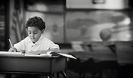 A young boy sits at his desk and works hard on school work