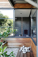 This ground floor bathroom, with walls of dark grey tadelakt decorated with a strip of mosaic tiles, opens onto a Japanese-style courtyard garden