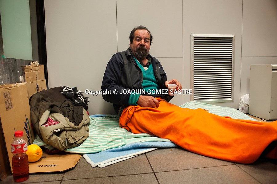 Miguel Angel ,52 years old and was born in Valladolid.at the ATM sleeping in Santander receives a hot coffee and fondled by volunteers municipal campaign of cold wave.photo © JOAQUIN GOMEZ SASTRE