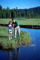 Father teaching daughter how to fish