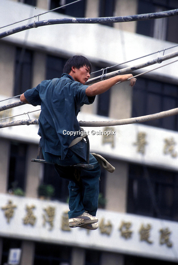 A Chinese electrician examines and repairs power cables in Guangzhou, China.