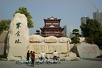 Huanggang, Hebei province, China - Cyclists read inscription of Hanshi Tie, a famous poem by Song dynasty poet and politician Su Dongpo at the Yiai Park, October 2014.