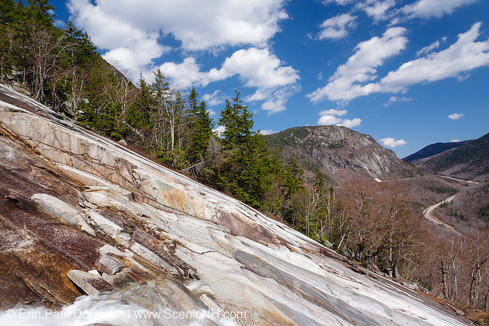 The rocky cliff of Mount Willard in Crawford Notch, New Hampshire from an exposed ledge on Mount Willey. The path of the old Maine Central Railroad and Route 302 are in view. During the winter season, this exposed ledge in the foreground is a popular ice climbing spot.