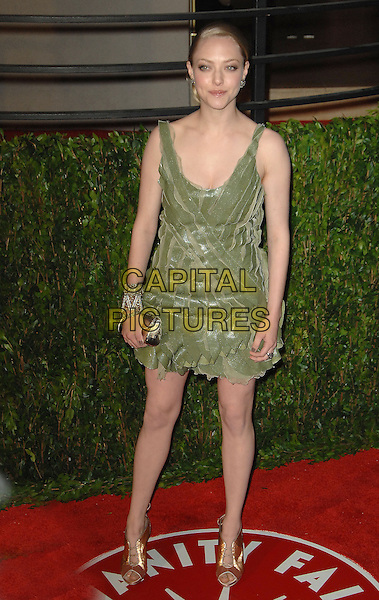 AMANDA SEYFRIED.The 2010 Vanity Fair Oscar Party held at The Sunset Tower Hotel in West Hollywood, California, USA..March 7th, 2010.full length green dress clutch bag gold shoes oscars.CAP/RKE/DVS.©DVS/RockinExposures/Capital Pictures.