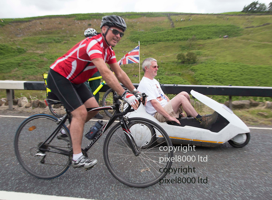 "Grand Depart - Tour de France 2014<br /> Yorkshire England.<br /> Second stage passes through ""Blubberhouses Moor""<br /> on the road from Harrogate<br /> Cycling fan in a Sinclair C5<br /> <br /> <br /> Pic by Gavin Rodgers/Pixel 8000 Ltd"