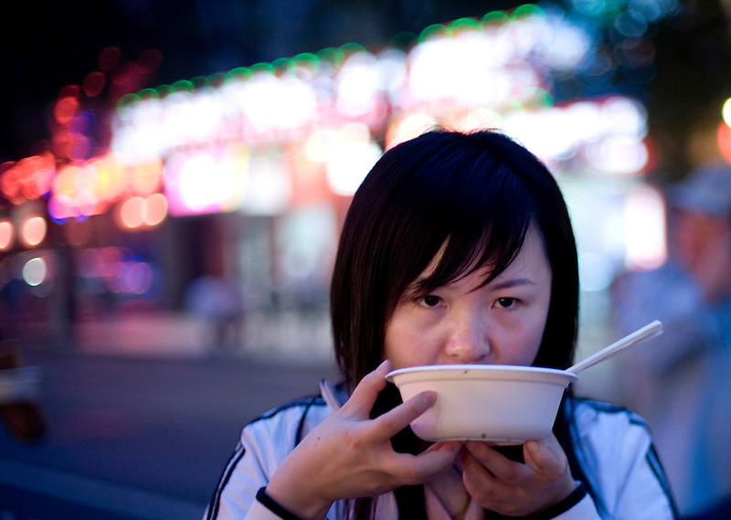 Chinese people eat dinner at Beijing's famous Donghuamen Night market, where one can sample many different specialty foods found throughout China.