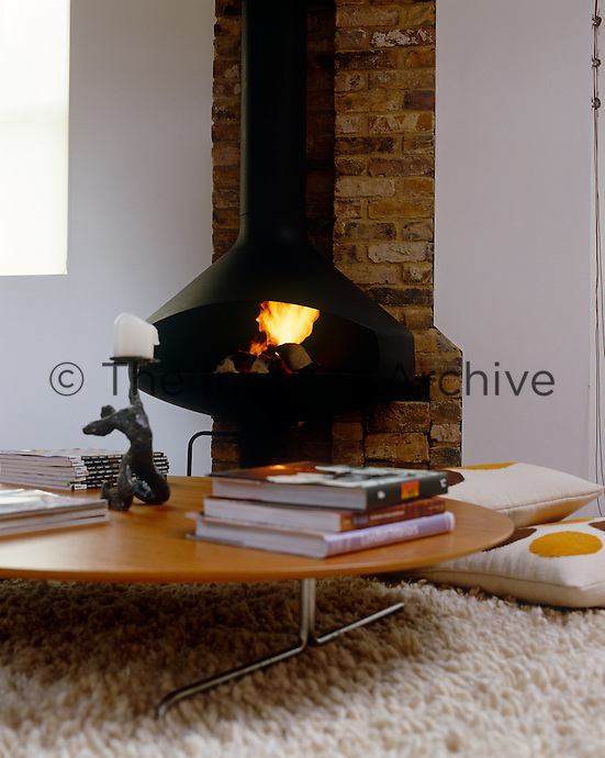 A 70's style shag-pile rug in front of a contemporary wood burning stove creates a cosy spot in the living room
