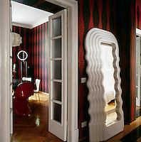 The hallway and dining room, with a red and black stripe pattern wallpaper and eclectic furnishings, combines pieces of Fifties and Sixties vintage furniture with neo-pop décor.