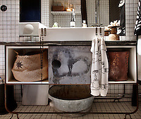 The washstand in the bathroom, made of rusted metal with a granite top, stores baskets and boxes of things neatly away