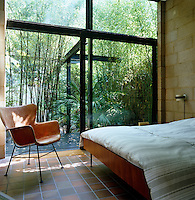 One wall of the master bedroom is made entirely of glass and has sliding doors that lead out to the rear garden planted with bamboo